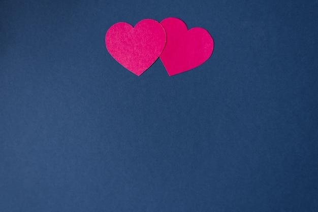コピーと暗い青色の背景に2つのピンクの心。バレンタインデーのパターン。愛の日のホリデーカード。折り紙