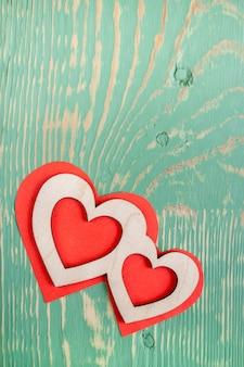 緑の織り目加工の木製テーブルに赤い紙の心に2つの彫刻が施された木製の心が横たわっています。上面図。