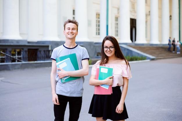 2 счастливых студента перед университетом с книгами и тетрадями
