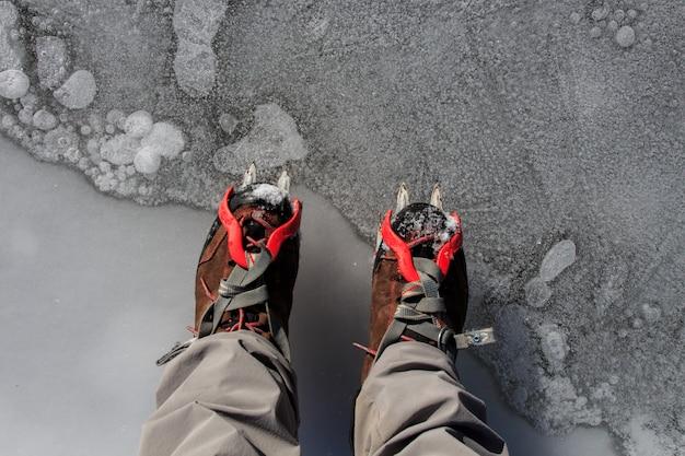 アイゼンを氷の上に置いた2つのハイキングブーツ。マウンテンスポーツアクセサリーのコンセプト