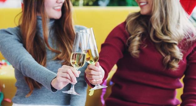 シャンパングラスを保持している2人の若い女性と笑顔で乾杯します。お祝いと挨拶の概念