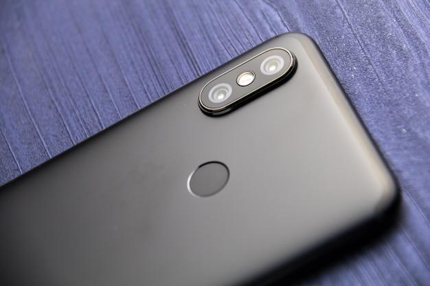 2台のカメラと指紋リーダーを備えた黒いスマートフォン。青い木製テーブルにデュアルカメラのスマートフォンをクローズアップ