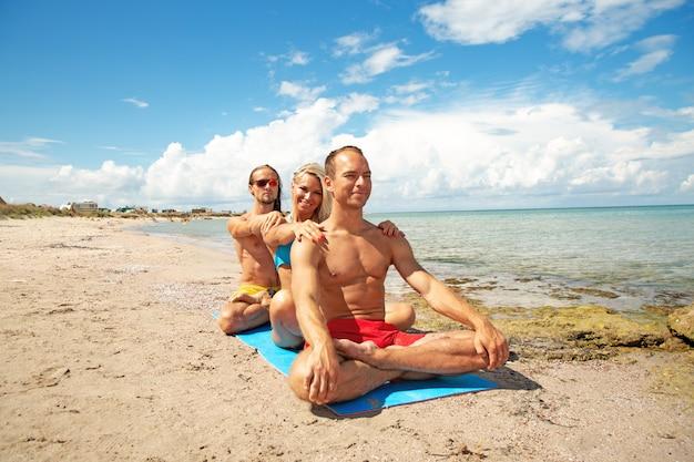 2つの若い男性と女性が一緒にフィットネスヨガの練習を行うビーチで。強度とバランスのためのアクロヨガ要素