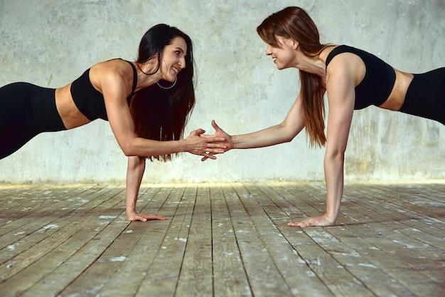 2人の若い女性がフィットネスルームでペア運動をしています。カメラでポーズをとって笑顔で、楽しい、素晴らしい雰囲気を持っています。