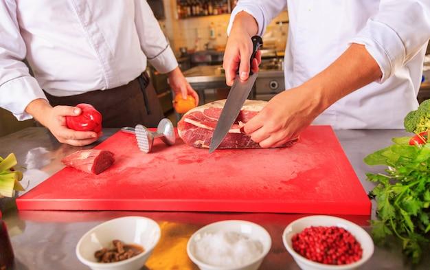 モダンなキッチンで料理を作るクック制服で2つの働く男性の肖像画