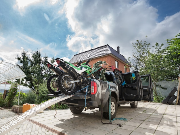 青い安全ベルトを使用してピックアップトラックのベッドに2つのスポーツダートバイクを固定する若い男。