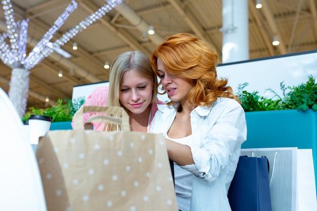 2つの美しい女性の友人は、販売中に購入した後、カフェに座っています。