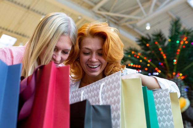 ショッピングセンターのバッグをチェックで2つの美しい若い女性