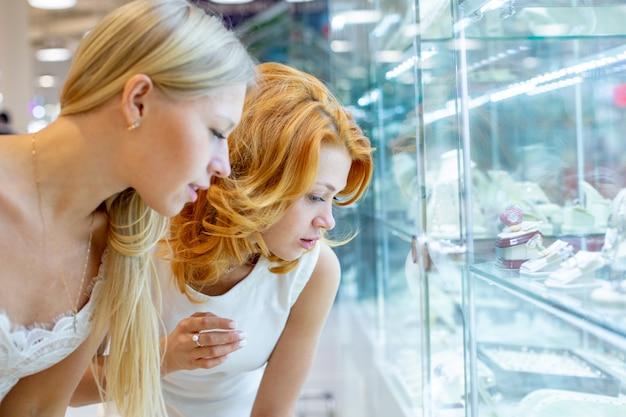 2人の女の子がジュエリーショップの表示ウィンドウを見ています。