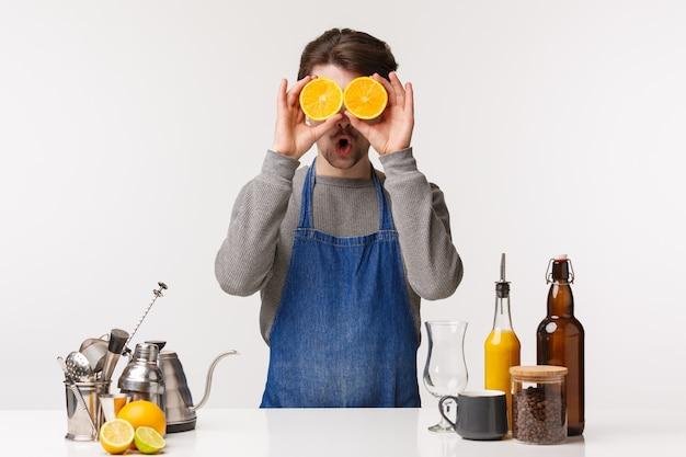 バリスタ、カフェワーカー、バーテンダーのコンセプト。エプロンでおかしな面白がって男性のビジネスオーナーがコーヒーや飲み物を作ったり、だましたり、目のように2つのオレンジスライスを抱えたり、ショックを受けた表情を作ったり