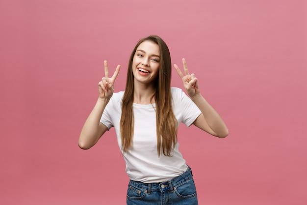 2本の指を示す陽気なトレンディな女性の肖像画はピンクの背景に署名します。