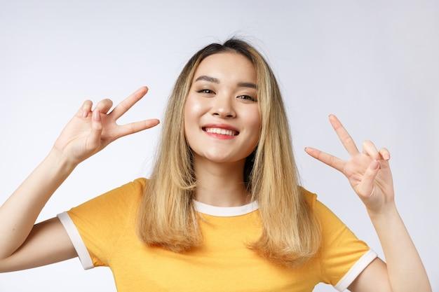 2本の指または勝利のジェスチャーを示す幸せな若いアジア女