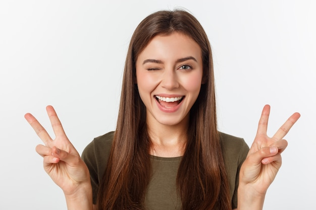 白の2本の指、肯定的なまたは平和のジェスチャーを示す若い女性。