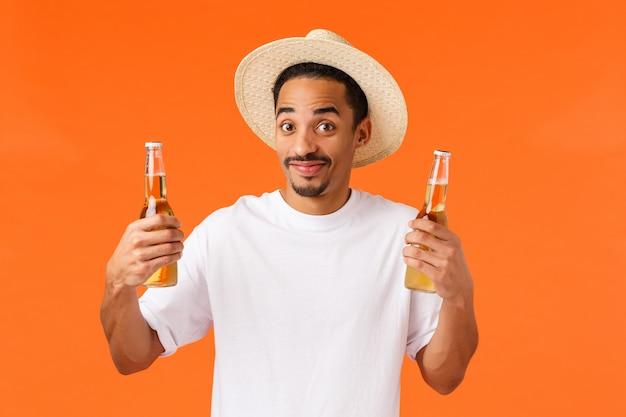 ビール2本を保持している幸せなアフリカ系アメリカ人のフレンドリーな男
