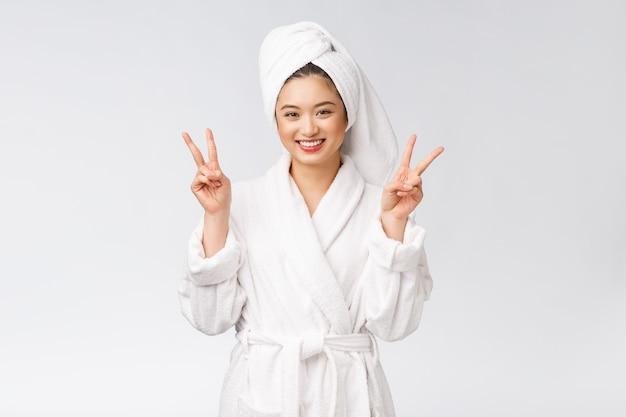 平和の兆しまたは幸せな気持ちで分離された2本の指を示す美しいアジアの女性