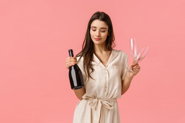 非常に幸せな魅力的な若いブルネットの少女のドレス、シャンパンボトルと2つのメガネを保持し、官能的に笑顔、バレンタインデーのロマンチックなデートを準備、喜んでピンクの壁に立って