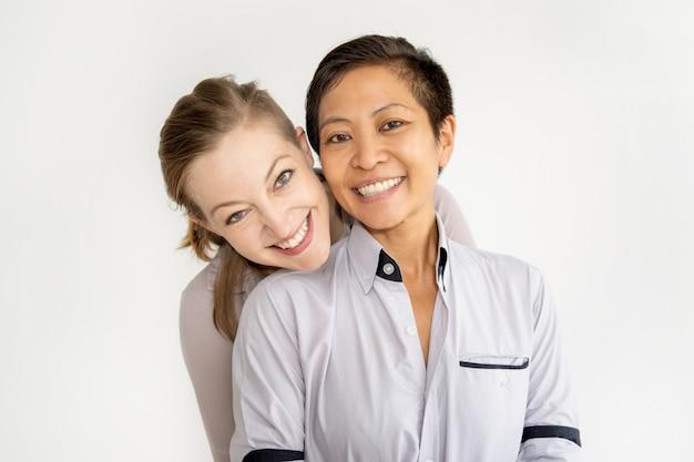 抱きしめるとカメラを見て2人の肯定的な女性