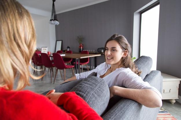 2人の女の子が家で会議をしている、チャットと笑い