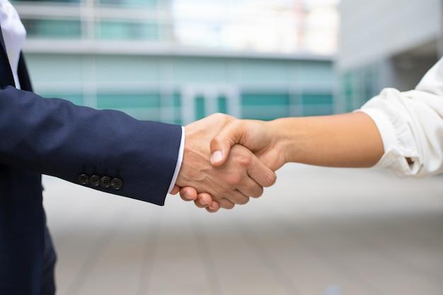 ビジネスハンドシェイクのクローズアップショット。握手する正式なスーツを着た2人のショットをトリミングしました。ビジネスハンドシェイクコンセプト