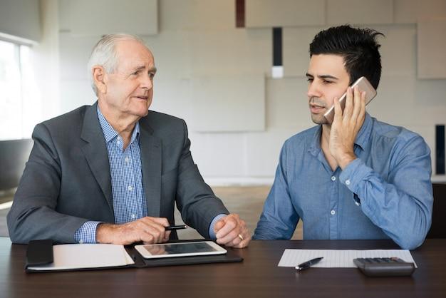 進行中のプロジェクトについて話し合っている2人の真剣な同僚