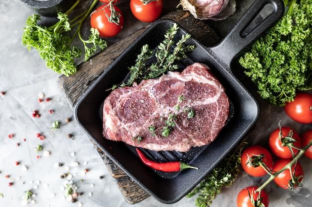 生の新鮮な肉。グリル鍋に材料、スパイス、野菜、ハーブを入れた2つのステーキ。上面図