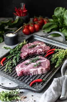生の新鮮な肉。グリル鍋に材料、スパイス、野菜、ハーブを入れた2人前のステーキ
