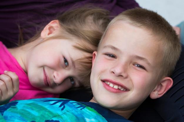 Портрет конца-вверх 2 малых милых белокурых счастливо усмехаясь детей, брата и сестры, мальчика и девушки кладя в кровать под красочным одеялом. небрежное невинное понятие дружбы детства и родных братьев.