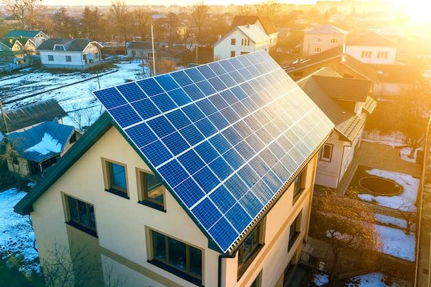 屋根の上の青い光沢のある太陽光発電システムと新しいモダンな住宅2階建て家コテージの空中のトップビュー。再生可能な生態学的なグリーンエネルギー生産の概念。