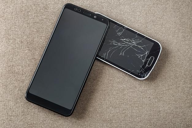 2つの黒い携帯電話、ひびの入った画面を持つ古い携帯電話と明るい布のコピースペースの背景に新しい現代の比較。技術の進歩と交換のコンセプト。