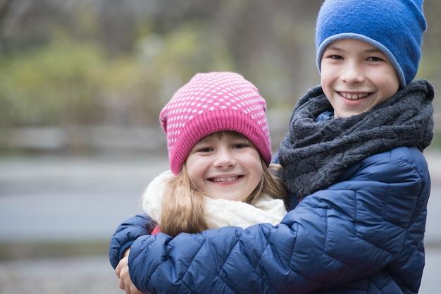 寒い秋や冬の天候で暖かい服を着て屋外でお互いをハグする2人の子供の男の子と女の子。