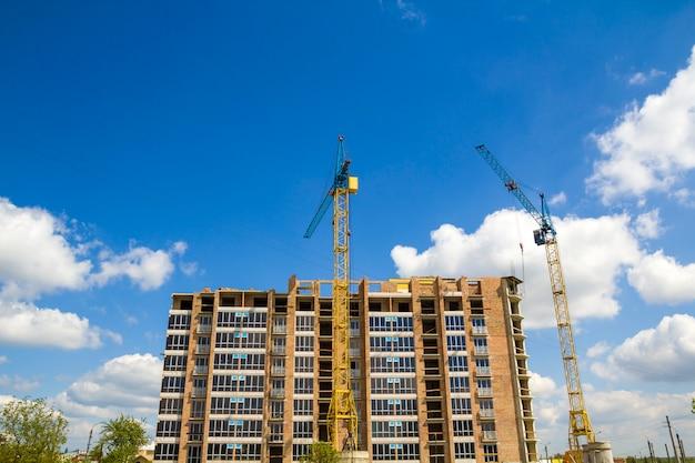 明るい青い空と緑の木々のシーンで新しいレンガの背の高い建物の建設で働く2つの産業タワークレーンのサイトを構築します。