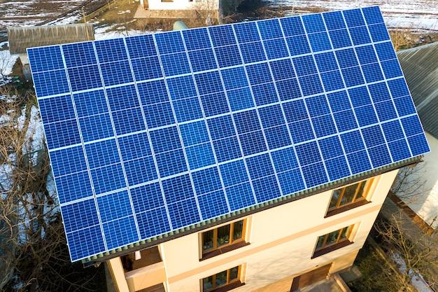 屋根の上の青い光沢のある太陽光発電システムと新しいモダンな2階建ての家のコテージの空撮。再生可能な生態学的なグリーンエネルギー生産の概念。