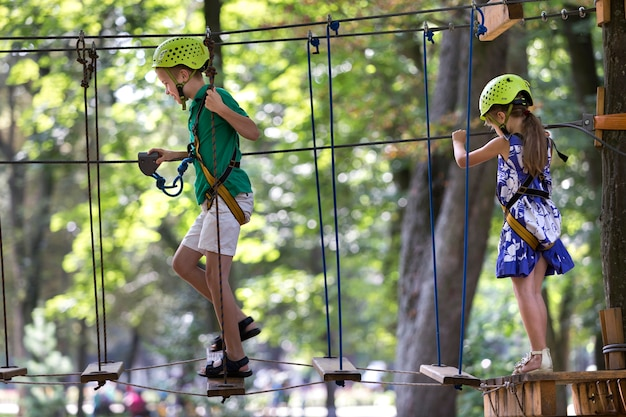 2人の子供、男の子と女の子の保護ハーネスとロープの方法で登山活動の安全ヘルメット。