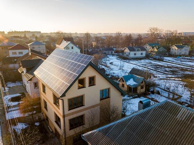 屋根に青い光沢のある太陽光発電パネルシステムを備えた新しいモダンな2階建ての家のコテージの空撮。再生可能な生態学的なグリーンエネルギー生産の概念。