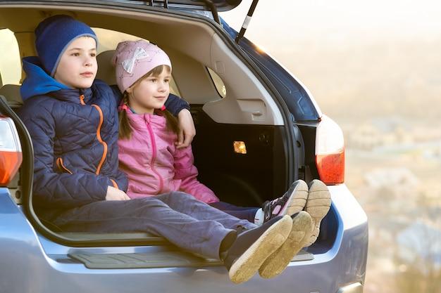 2人の幸せな子供の男の子と女の子が車のトランクに一緒に座っています。陽気な兄と妹が家族の車のトランクルームでお互いをハグします。週末旅行や休日のコンセプトです。