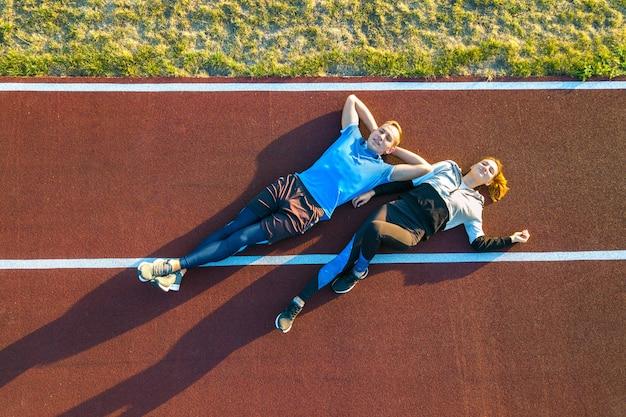 2人の若者のスポーツマンとスポーツウーマンが夏にマラソンをジョギングした後休んでいるスタジアムフィールドの赤いゴムのランニングトラックの上に敷設の空撮をトップダウンします。