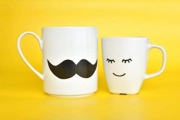 2つの感情的なコーヒーカップが一緒に立つ、幸せなバレンタインの日の概念。