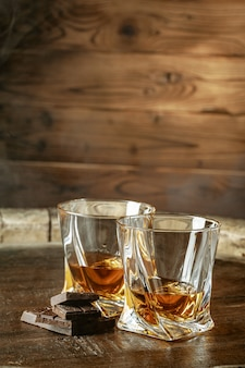 2杯のバーボンまたはスコッチ、またはブランデーとダークチョコレートの破片