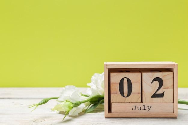 2 июля деревянный, квадратный календарь. деловая поездка или планирование отпуска