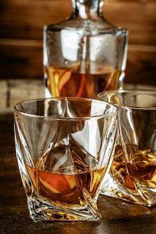 ブランデーまたはコニャックと木製のテーブルの上にボトルを2杯
