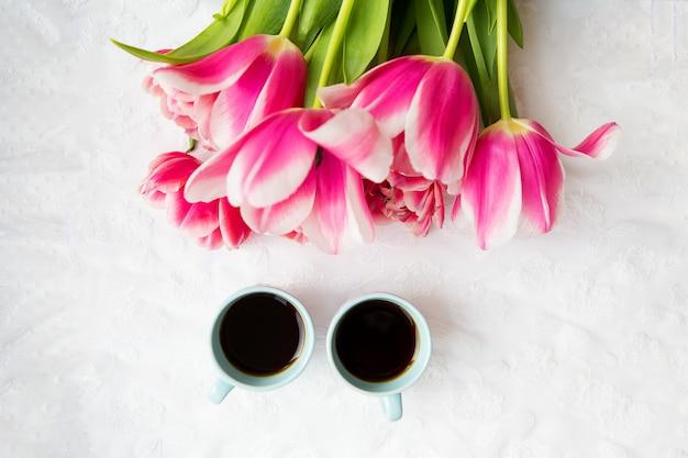コーヒー2杯とピンクのチューリップの花束