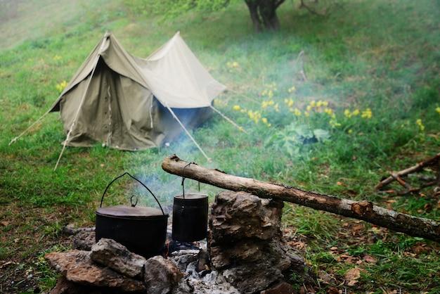 ツーリストキャンプのスタックで2つのボウラー、背景にテント