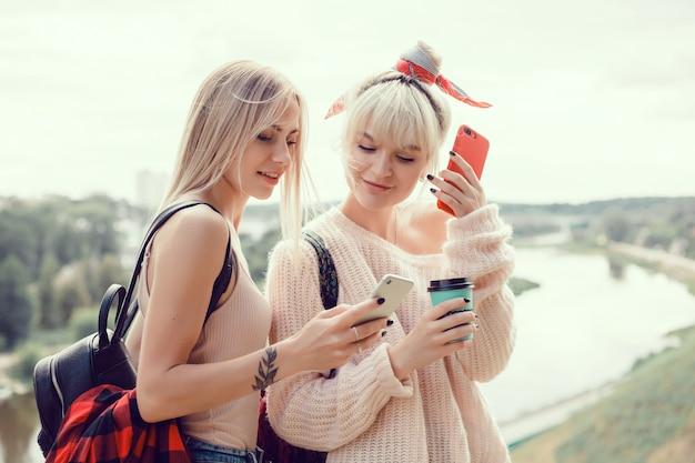 2人の若い女の子の姉妹が通りにポーズをとり、セルフをする