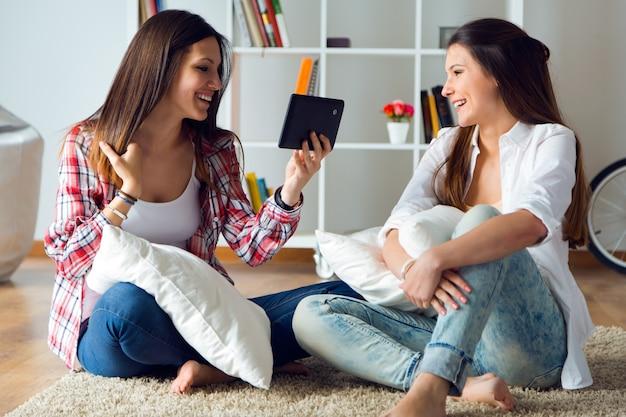 家庭でデジタルタブレットを使用している2つの美しい若い女性の友人。
