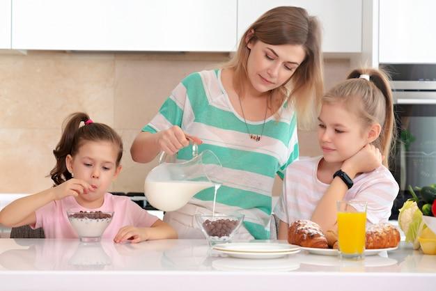 母は台所、幸せなシングルマザーコンセプトのテーブルで彼女の2人の娘に朝食を提供