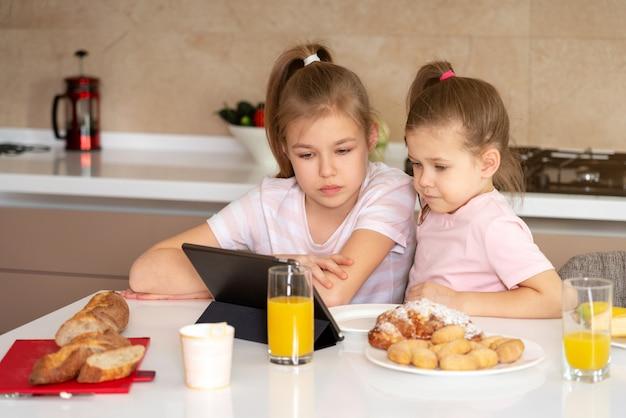 2人の姉妹が朝食をとり、一緒にタブレットで漫画を見て、幸せな家族の概念