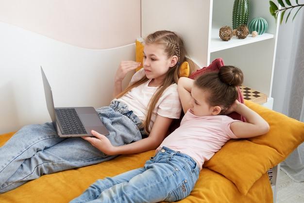 何かを見てラップトップを使用して一緒にベッドに横になっている2人の姉妹