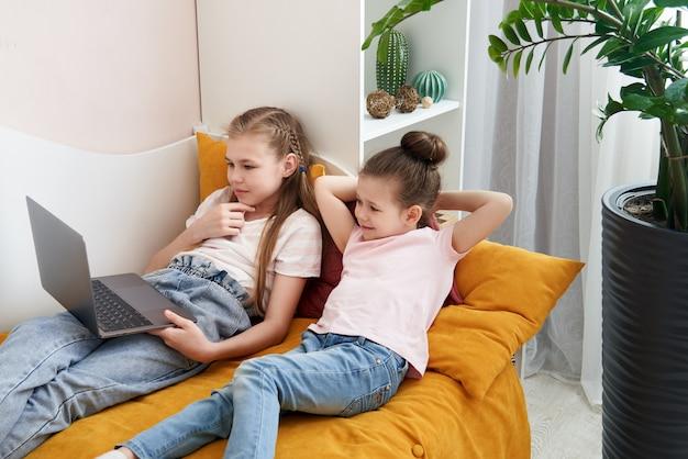 自宅のベッドに横になっているラップトップを使用して2つの幼い姉妹