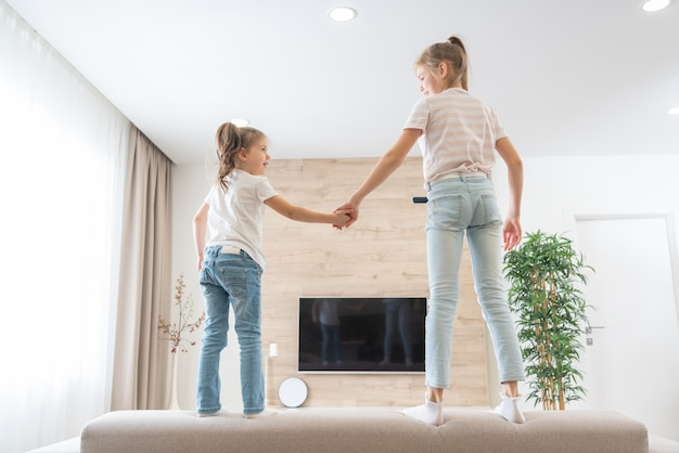 楽しいリビングルームのソファでジャンプする2人の姉妹