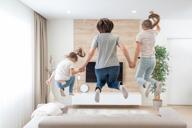 母と2人の娘がリビングルームのソファーにジャンプ